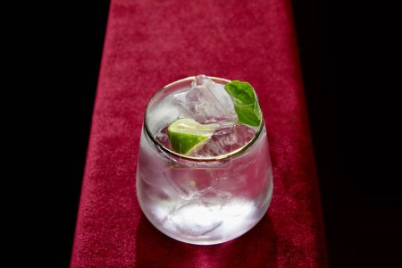 High angle view of glass with fresh mojito, mint and lime slice isolated on black