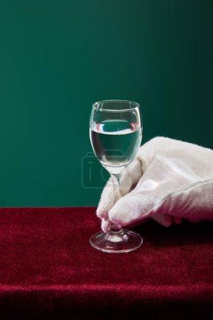 Photo pour Vue recadrée de la main dans le gant éponge tenant verre de tir avec liquide isolé sur vert - image libre de droit