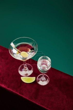 vue grand angle du verre à shooter et du verre à cocktail avec vermouth, tranche de citron vert et olive entière sur cure-dent sur surface velours isolée sur fond vert