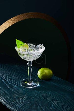 Photo pour Vue grand angle du verre à cocktail avec glace, feuille de menthe et citron vert entier sur fond de bois bleu - image libre de droit