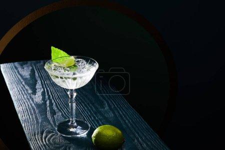 Photo pour Vue à grand angle d'un verre de cocktail avec un verre avec glaçons, feuille de menthe et chaux entière sur une surface en bois bleu sur fond noir. - image libre de droit