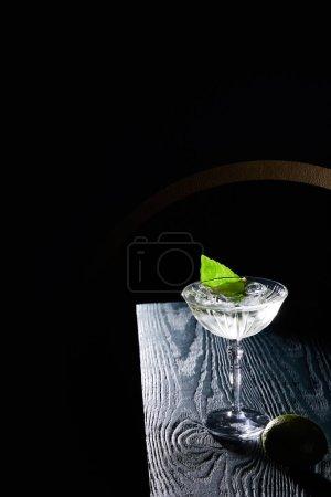 Photo pour Vue grand angle du verre à cocktail avec boisson avec glaçons, feuille de menthe et chaux entière sur une surface en bois bleu sur fond noir avec des lignes géométriques - image libre de droit