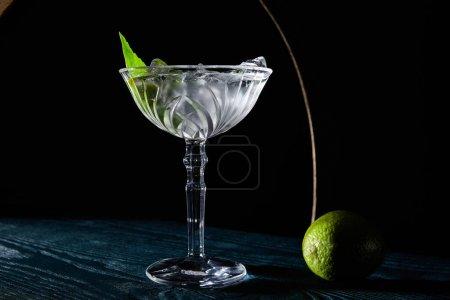 Photo pour Verre à cocktail avec boisson avec glaçons, feuille de menthe et citron vert entier sur une surface en bois bleu sur fond noir avec des lignes géométriques - image libre de droit