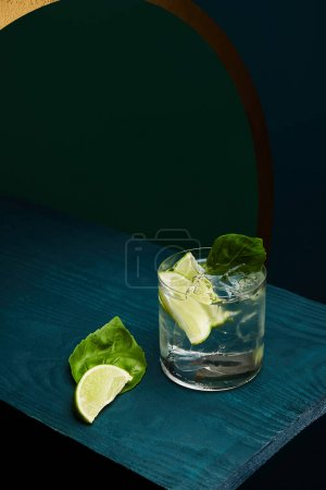 Photo for High angle view of old fashioned glass with fresh drink, mint leaf and lime slice on blue wooden surface on green and blue geometric background - Royalty Free Image
