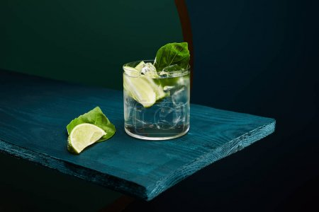 old fashioned glass with fresh drink, mint leaf and lime slice on blue wooden surface on green and blue geometric background
