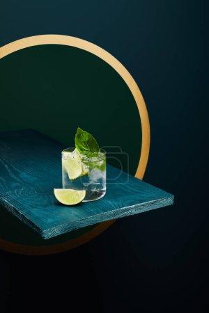 Photo pour Vue à grand angle de verre à l'ancienne avec boisson fraîche, feuille de menthe et tranche de chaux sur une surface bleue en bois sur fond vert et bleu géométrique avec cercle doré. - image libre de droit