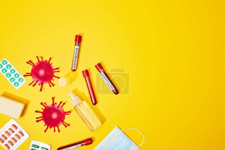 Photo for Top view of test tubes with coronavirus test lettering near medical mask, blister packs with pills, bottle with antibacterial liquid and soap bar on yellow - Royalty Free Image