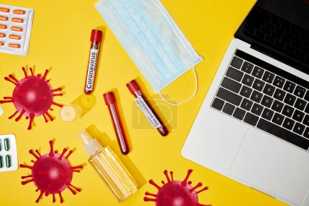 Photo for Top view of test tubes with coronavirus lettering near medical mask, pills, bottle with antibacterial liquid and laptop on yellow - Royalty Free Image