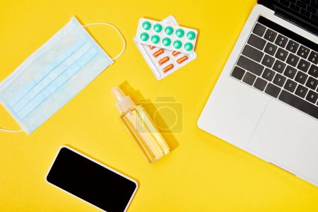 Photo for Top view of laptop and smartphone with blank screen near pills, medical mask and bottle with hand sanitizer on yellow - Royalty Free Image