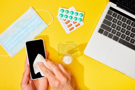 Photo for Top view of man holding napkin near smartphone with blank screen, laptop, pills, hand sanitizer and medical mask on yellow - Royalty Free Image