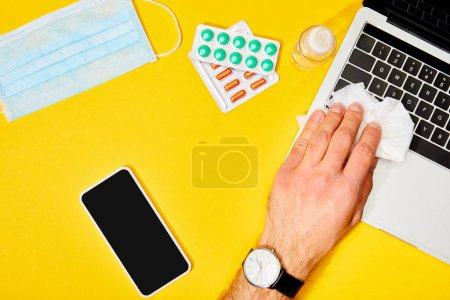 Photo for Top view of man holding napkin near laptop, smartphone with blank screen, pills, hand sanitizer and medical mask on yellow - Royalty Free Image