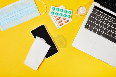 Photo for Top view of laptop and smartphone with blank screen near napkin, pills, medical mask and bottle with hand sanitizer on yellow - Royalty Free Image