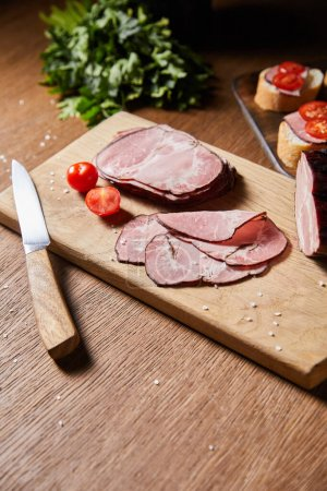 Photo pour Foyer sélectif de tranches de jambon savoureux, tomates cerises et couteau sur planche à découper près de persil et canape - image libre de droit