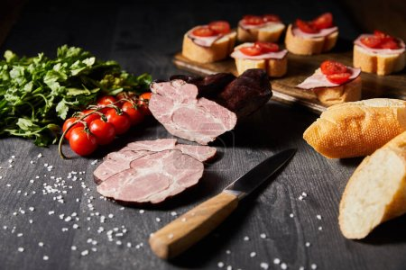 Photo pour Foyer sélectif de jambon tranché savoureux jambon, tomates cerises, persil, sel, couteau et baguette sur table grise en bois avec canape - image libre de droit