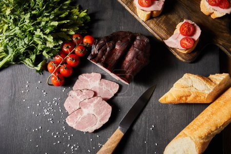 Photo for Top view of tasty ham sliced ham, cherry tomatoes, parsley, salt, knife and baguette on wooden grey table with canape - Royalty Free Image