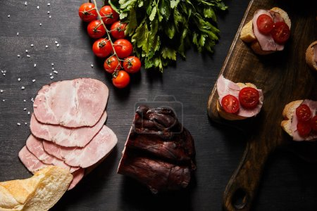 Photo for Top view of tasty ham sliced ham, cherry tomatoes, parsley, salt and baguette on wooden grey table with canape - Royalty Free Image