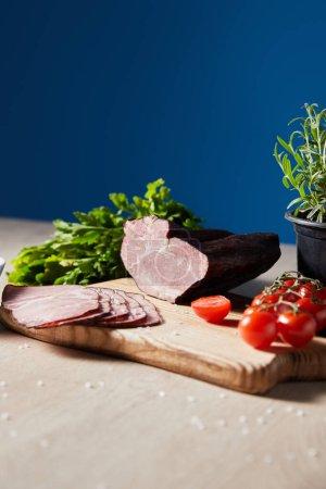 Photo pour Foyer sélectif de jambon savoureux sur planche à découper avec persil, tomates cerises sur table en bois sur fond bleu - image libre de droit
