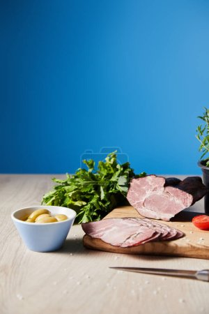 selective focus of tasty ham on cutting board with knife, parsley, olives on wooden table on blue background