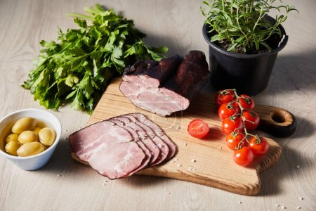 Photo for Tasty ham on cutting board with greens, cherry tomatoes, olives on wooden table - Royalty Free Image