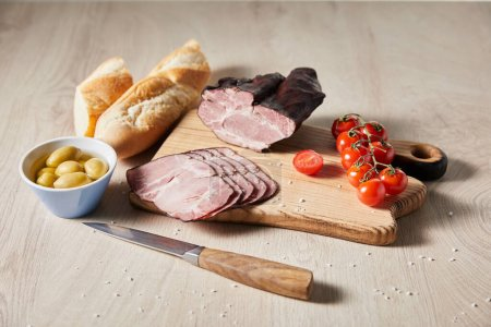 selective focus of tasty ham on cutting board with knife, cherry tomatoes, olives and baguette on wooden table
