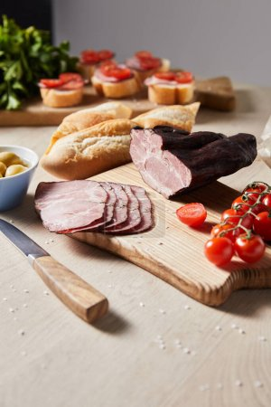Photo for Selective focus of tasty ham on cutting board with knife, parsley, cherry tomatoes, olives and baguette near canape on wooden table - Royalty Free Image