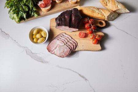 Photo for Top view of tasty ham on cutting board with parsley, cherry tomatoes, olives and baguette on white marble surface - Royalty Free Image
