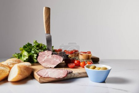selective focus of knife in tasty ham on cutting board with parsley, cherry tomatoes, olives and baguette on white surface isolated on grey