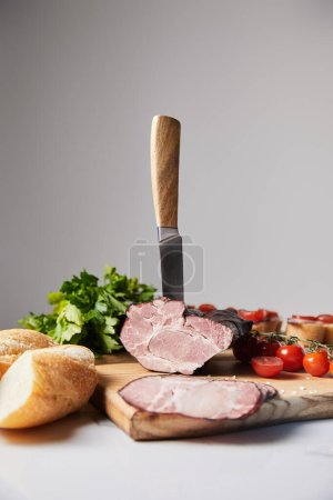 Photo for Selective focus of knife in tasty ham on cutting board with parsley, cherry tomatoes and baguette on white surface isolated on grey - Royalty Free Image