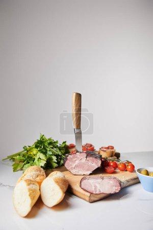 Photo pour Foyer sélectif du couteau dans le jambon savoureux sur planche à découper avec persil, tomates cerises et baguette sur surface blanche isolé sur gris - image libre de droit