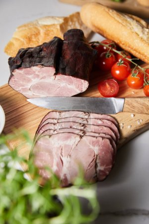 selective focus of tasty ham on cutting board with knife, cherry tomatoes and baguette