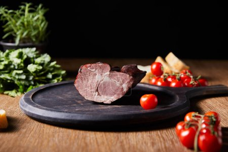 selective focus of tasty ham on board near parsley, cherry tomatoes and baguette on wooden table isolated on black
