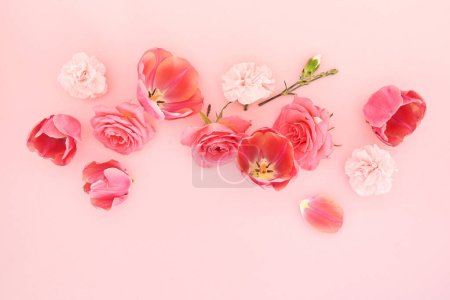 top view of blooming spring flowers on pink background