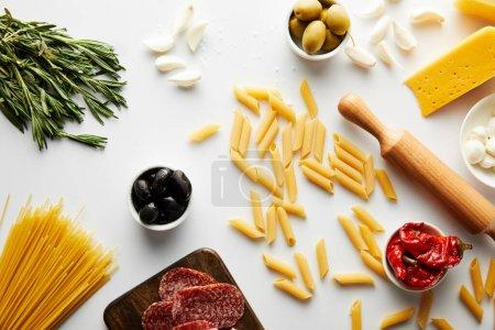 Draufsicht auf Nudelholz, Nudeln, Rosmarin und Fleischplatte mit Zutaten auf weißem Hintergrund