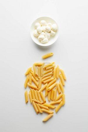 Photo pour Vue du dessus des pâtes et bol avec mozzarella sur fond blanc - image libre de droit