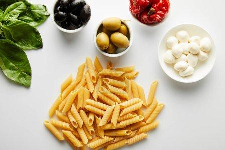 Photo pour Vue du dessus des pâtes près des feuilles de basilic et des bols avec des ingrédients sur fond blanc - image libre de droit