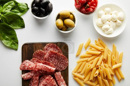 Photo for Top view of meat platter, pasta, basil leaves and bowls with ingredients on white background - Royalty Free Image