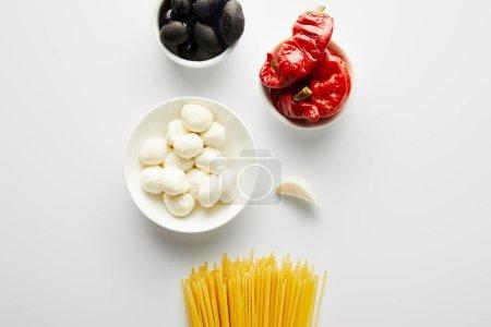 Draufsicht auf Spaghetti, Knoblauch und Schalen mit Zutaten auf weißem Hintergrund
