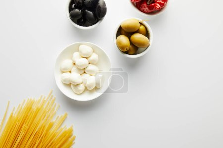 Photo for Top view of spaghetti and bowls with ingredients on white background - Royalty Free Image