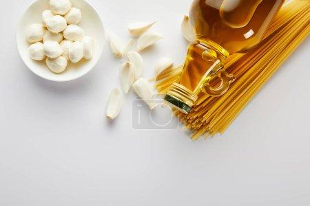 Draufsicht auf Knoblauch, Schüssel mit Mozzarella, Spaghetti und einer Flasche Olivenöl auf weißem Hintergrund