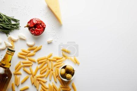 Draufsicht auf eine Flasche Olivenöl, Nudeln, Käse und Zutaten auf weißem Hintergrund