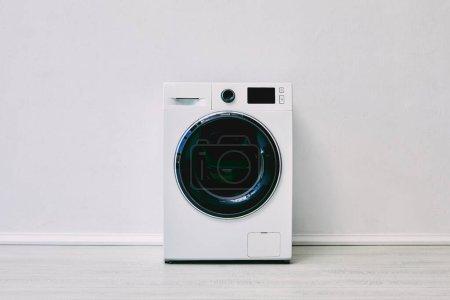 Photo pour Machine à laver moderne près du mur blanc dans la salle de bain - image libre de droit