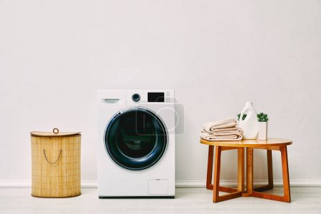 modern washing machine near laundry basket, coffee table with towels, detergent bottle and plant in bathroom
