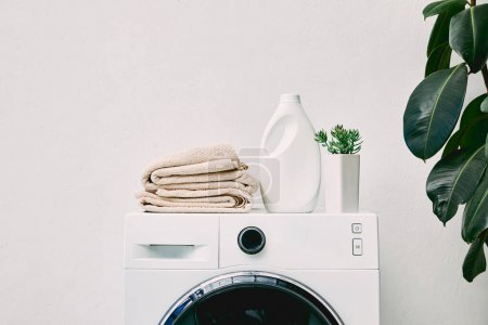 Photo for Detergent bottle and towels on washing machine and green plant in bathroom - Royalty Free Image