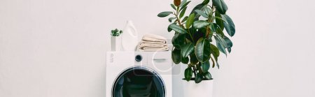 Photo pour Vue panoramique de la salle de bain moderne avec des plantes près de la bouteille de détergent et des serviettes sur machine à laver - image libre de droit