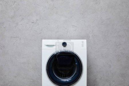Photo pour Machine à laver moderne près du mur texturé gris dans la salle de bain - image libre de droit