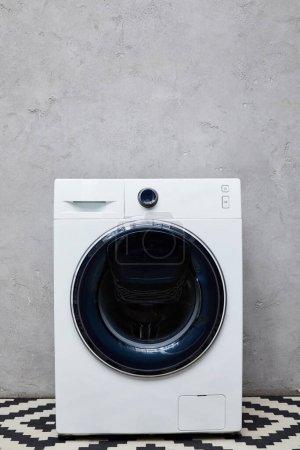 washing machine near grey wall in bathroom