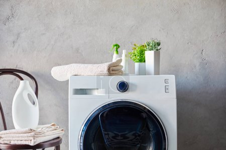 detergent and spray bottles on washing machine near plants, towels and chair in bathroom