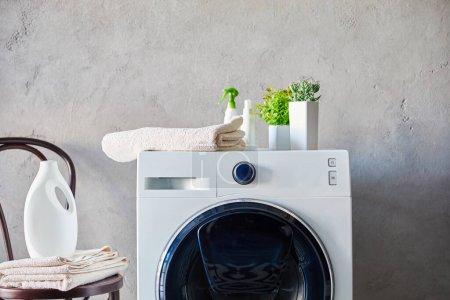 Photo pour Bouteilles de détergent et de pulvérisation sur la machine à laver près des plantes, serviettes et chaise dans la salle de bain - image libre de droit