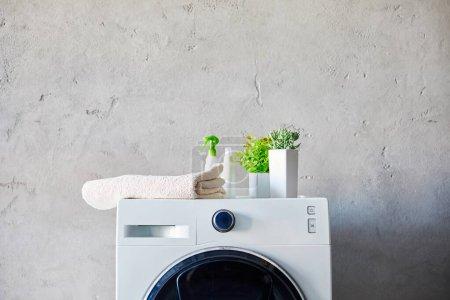 Photo pour Plantes, serviette et bouteilles sur lave-linge dans la salle de bain - image libre de droit