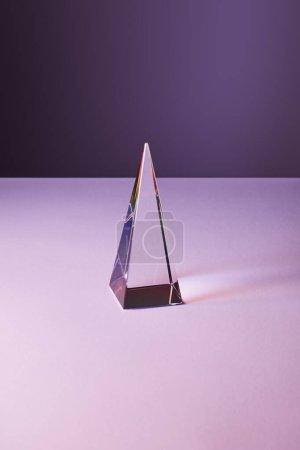 Photo pour Pyramide transparente cristal avec réflexion de la lumière sur fond violet et violet - image libre de droit